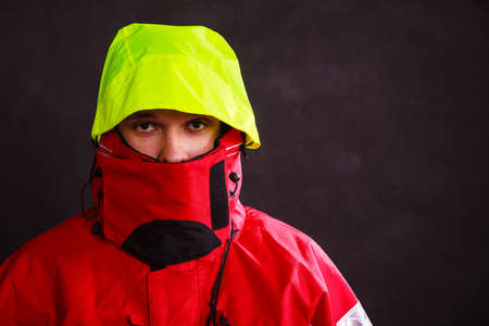 outdoorsman: Male outdoorsman with covered face. Young man wearing waterproof oilskin. Adventure outdoor action danger concept.