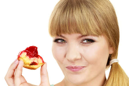 fattening: Woman holds cake cupcake in hand taking a huge bite out of dessert, eating unhealthy junk food. Sweetness indulging and fattening concept Stock Photo