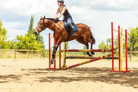 jumping fence: Mujer activa chica entrenamiento jinete equitación saltar sobre la cerca. Competición deporte ecuestre y actividad.