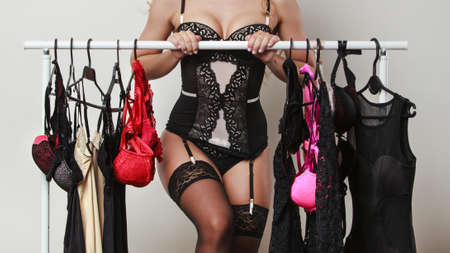 Shopping for evening romance. Gorgeous attractive sexy woman buying lingerie. Seductive woman wearing black tempting underwear on shopping.
