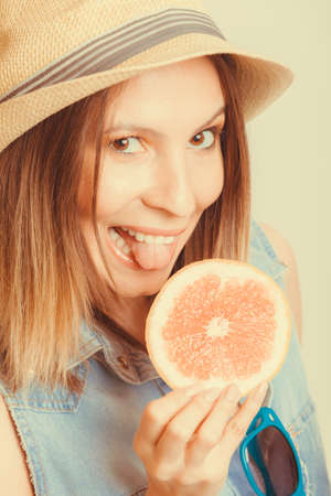glad: Happy glad woman tourist in straw hat drinking grapefruit juice. Healthy diet food. Weight loss. Summer vacation holidays.