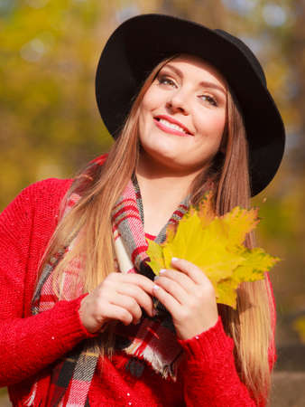 big leafs: Portrait of attractive young smiling woman holding big gold leafs in autumnal park. Fashionable girl wearing red sweater scarf and black hat.