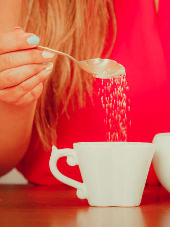 adding sugar: Closeup of human adding sugar to tea or coffee at home. Person with hot beverage relaxing in kitchen. Stock Photo