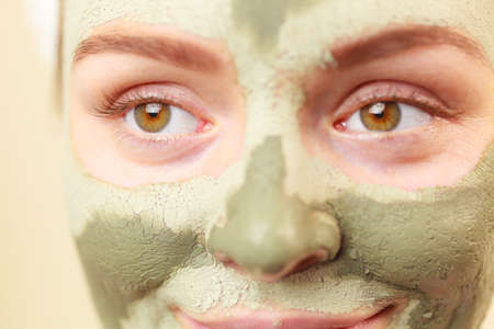 mud woman: Skin care. Woman face with green clay mud mask close up. Girl taking care of oily complexion. Beauty treatment.