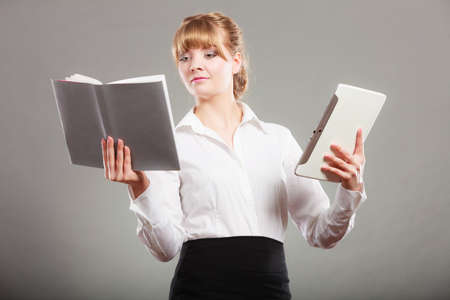 ebook: Woman learning with ebook reader and book. Choice between modern educational technology and traditional way method. Girl holding digital tablet pc and textbook. Contemporary education.