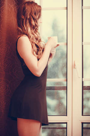 energizing: Pensive woman in lingerie drinking cup of coffee looking through french door window at home. Young girl with hot energizing beverage stay awake. Caffeine energy.