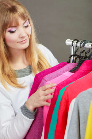 bought: Pretty happy woman choosing which clothing wear from wardrobe. Young undecided shopper girl bought new clothes. Shopping sale concept. Stock Photo