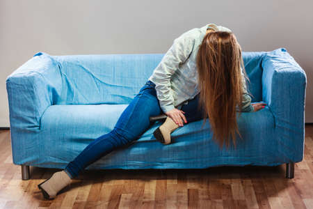 home life: Sad depressed woman on sofa at home. Breakdown and negative emotion. Unhappy girl sitting on couch.