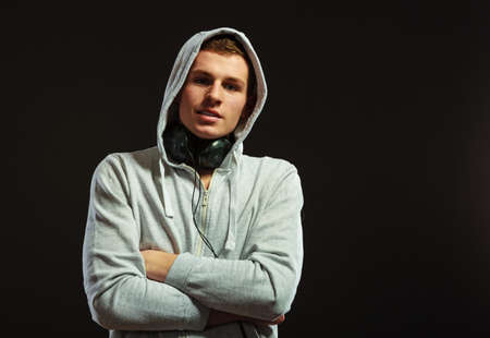 cool guy: young serious hooded man teen boy with headphones listening to music black background