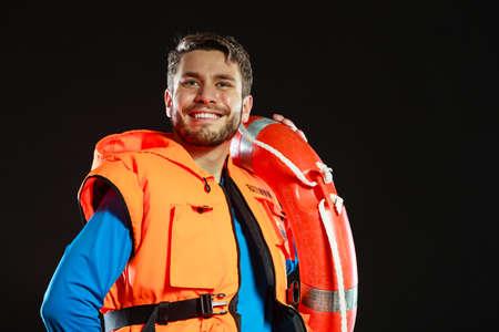 Rettungsschwimmer in Schwimmweste Jacke mit Ringboje Rettungsring. Man Überwachung Schwimmbadwasser auf schwarz. Unfallverhütung. Standard-Bild