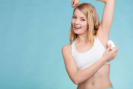 hygiene: Daily skin care and hygiene. Girl applying stick deodorant in armpit. Young woman putting antiperspirant in underarms on blue
