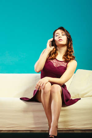 mobile communication: Technology and communication. Elegant young woman sitting on couch talking on mobile phone. Blue background