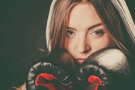 intimidating: Fighting boxing and defense. Sportsmanship and strong body. Young woman wear sportswear and boxing gloves cover face look at opponent. Stock Photo
