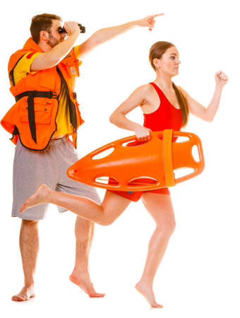 float tube: Lifeguards with rescue tube buoy and life vest jacket looking through binoculars. Man and woman supervising swimming pool running. Accident prevention.