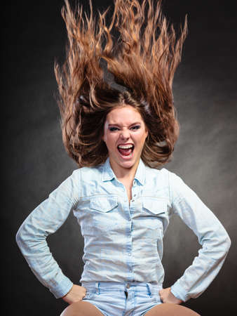 ecstatic: Happy and ecstatic woman having fun. Carefree young girl with long hair in motion. Wind. Stock Photo