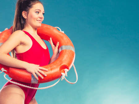 buoy: Lifeguard with ring buoy lifebuoy. Woman girl supervising swimming pool water on blue. Accident prevention rescue. Stock Photo