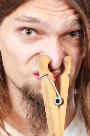 unpleasant: Man with clothespin clip peg on his nose. Young long haired guy feeling unpleasant odor stink. Bad smell concept.