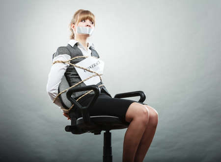bondage girl: Afraid businesswoman bound by contract terms and conditions with mouth taped shut. Scared woman tied to chair become slave. Business and law concept. Stock Photo