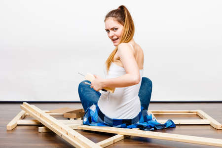 muebles de madera: Mujer montaje de muebles de madera con un destornillador. Aficionado al bricolaje. Niña haciendo mejoras para el hogar. Vista posterior trasera.