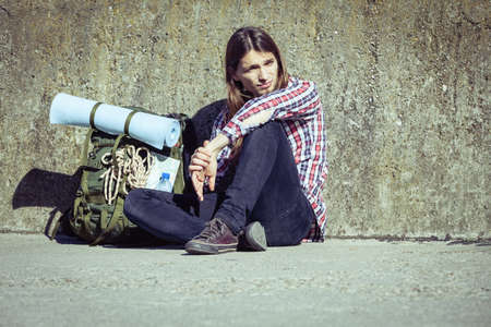 tramping: Man tourist backpacker relaxing outdoor sitting tired by grunge wall. Adventure, summer, tourism active lifestyle. Young hipster guy tramping Stock Photo
