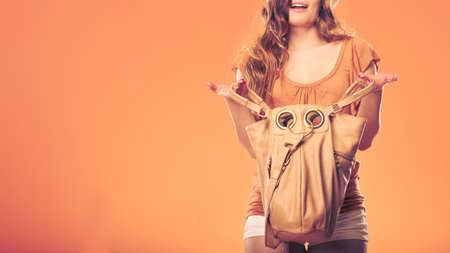 handbag: Fashionable woman wearing hat searching through handbag. Girl looking for something. Summer fashion. Holidays vacation.