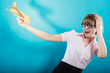 bother: Fly fear metaphor, aerophobia concept. Business woman holding airplane in hand vivid blue background