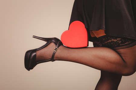 sexualidad: La belleza, la sexualidad y la seducción. Mujer parte del cuerpo sexy con un vestido negro y medias de las bragas con la caja de regalo presente corazón rojo acostado en las piernas zapatos de tacón alto. estudio de disparo. Foto de archivo