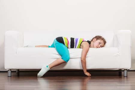 Müde erschöpft faul kleines Mädchen, das auf Sofa zu Hause. Sleepy Kind ruhelosigkeit auf Couch sich entspannt. Standard-Bild - 55211647