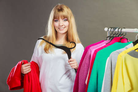 hand wear: Pretty happy woman with hanger in hand choosing which clothing wear from wardrobe. Young undecided shopper girl bought new clothes. Shopping sale concept.