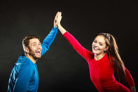 Man and woman giving high five. Smiling couple friends celebrating success achievement in studio on black.