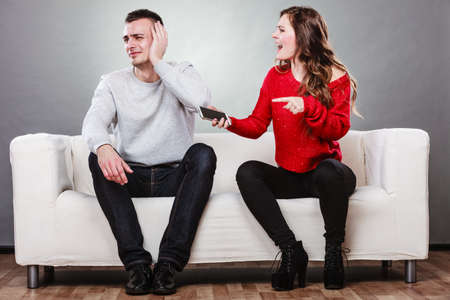 lovers quarrel: Angry furious wife shouting at husband showing text messages from lover mistress on his mobile phone. Outraged girlfriend find out about boyfriend affair romance betrayal. Cheating man covering ears.