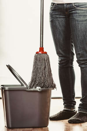 cleanup: Closeup of human cleaning mopping floor. Person with mop and bucket at home. House cleanup. Stock Photo