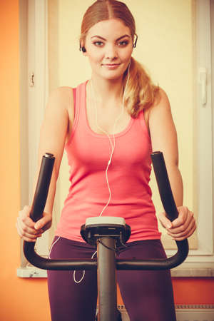 escucha activa: Active joven que se resuelve en la bici de ejercicio en bicicleta estacionaria. Formaci�n Muchacha deportiva en casa escuchando m�sica. Fitness y concepto de p�rdida de peso.