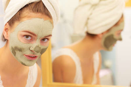 mud girl: Skin care. Woman in bathroom with green clay mud mask on face looking at mirror. Girl taking care of oily complexion. Beauty treatment. Stock Photo