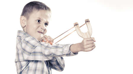harass: Children upbringing problems. Kid holding slingshot in hands. Bad naughty boy shoots from a wooden sling on white