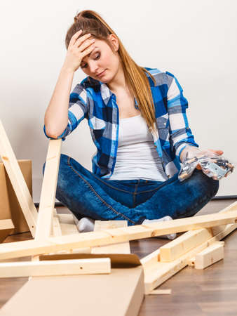 enthusiast: Stressed woman assembling wooden furniture. DIY enthusiast holding screws and parts. Young girl doing home improvement.
