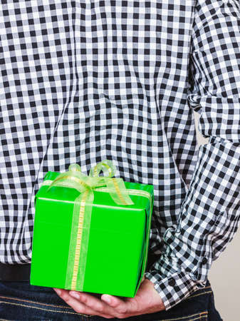 gift behind back: Man hiding green gift box with white ribbon behind back. Closeup of male hand holding christmas present. Guy wearing flannel shirt. Birthday, holiday surprise.