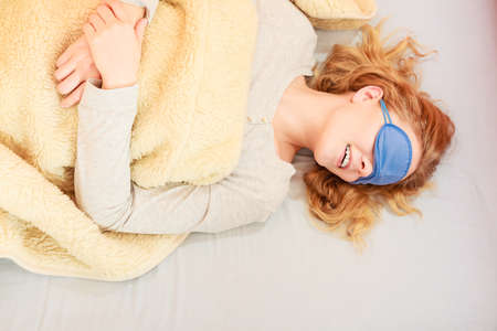 blindfold: Tired woman sleeping in bed under blanket wearing blindfold sleep mask. Young girl taking nap.