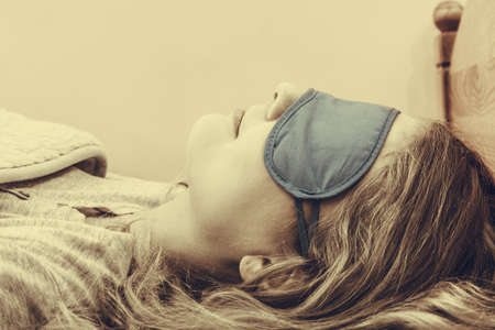 taking nap: Tired woman sleeping in bed wearing blindfold sleep mask. Young girl taking nap. Sepia.