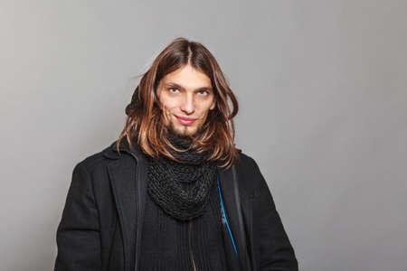 Retrato de hombre guapo de moda vistiendo abrigo negro y una bufanda. Individuo joven que presenta en estudio. Invierno o la moda de otoño.