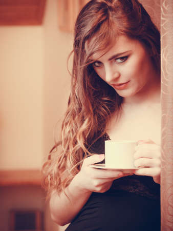 energizing: Woman drinking cup of coffee at home. Young girl with hot energizing beverage stay awake. Caffeine energy. Stock Photo