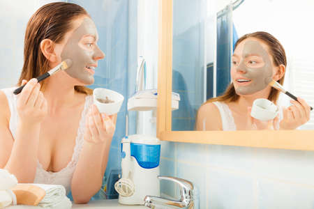 mud woman: Beauty skin care cosmetics and health concept. Young woman applying facial mud clay mask to her face in bathroom