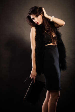 black boa: Party celebration carnival concept.  Magnificent long hair woman wearing black evening dress feather boa holds handbag in hand on dark Stock Photo