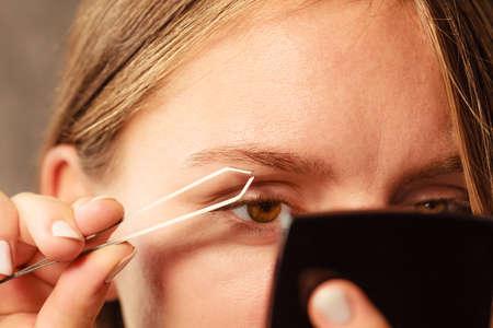 pluck: Woman plucking eyebrows depilating with tweezers closeup part of face. Girl tweezing eyebrows.