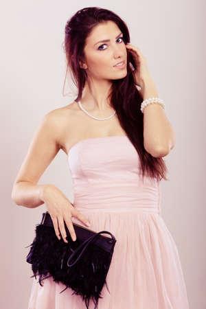 Bellezza, moda e gente elegante concetto - giovane donna bruna sottile in abito senza spalline luminoso tiene pochette nera