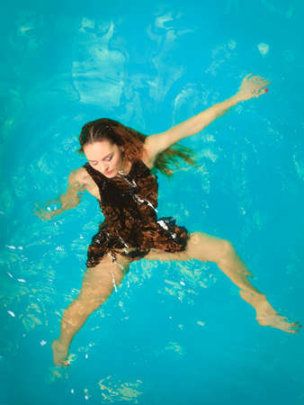 Woman relaxing at swimming pool. Young girl wearing black dress floating. Water aerobics fitness.
