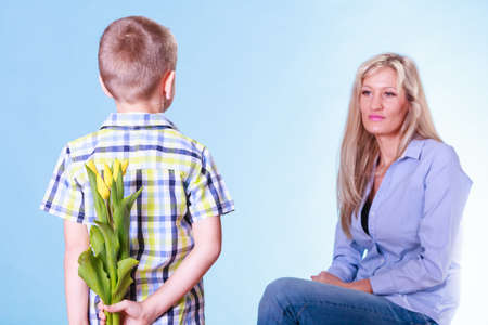 gift behind back: Special occasions holiday and mother day. Young boy prepare surprise gift flowers hold tulips behind back mother sit smiling.