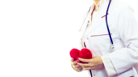 proffesional occupation: Periodic examinations. Cardiology concept. Female cardiologist holding red heart. Doctor with stethoscope and white medical apron uniform. Isolated on white.