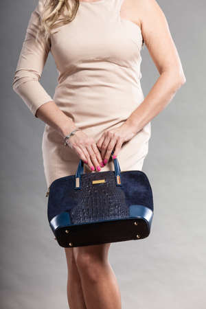 body bag: Clothing and accessories. Fashionable woman wearing dress and holding black elegant bag. Part body of mid aged lady on gray.
