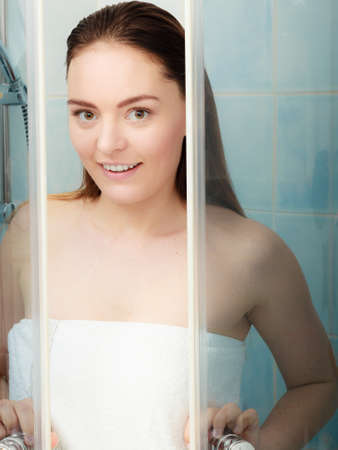 enclosure: Girl showering in shower cabin cubicle enclosure. Young woman with white towel taking care of hygiene in bathroom. Stock Photo